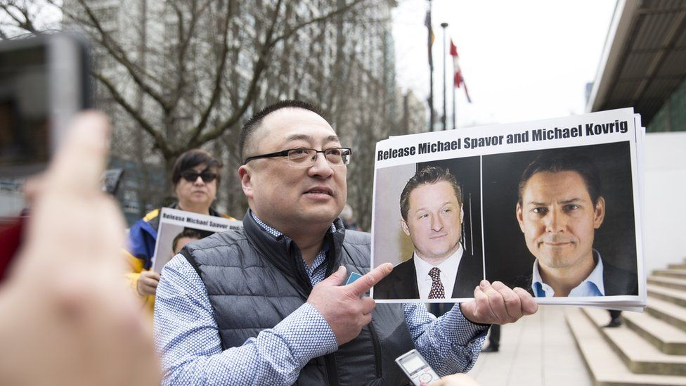 A China pro-democracy protester holds photos of Canadians Michael Spavor and Michael Kovrig