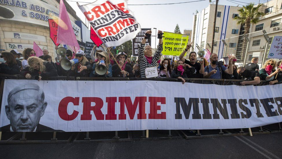 "Protesters hold up a banner saying ""crime minister"" near the Jerusalem court ahead of the resumption of Benjamin Netanyahu's corruption trial (5 April 2021)"
