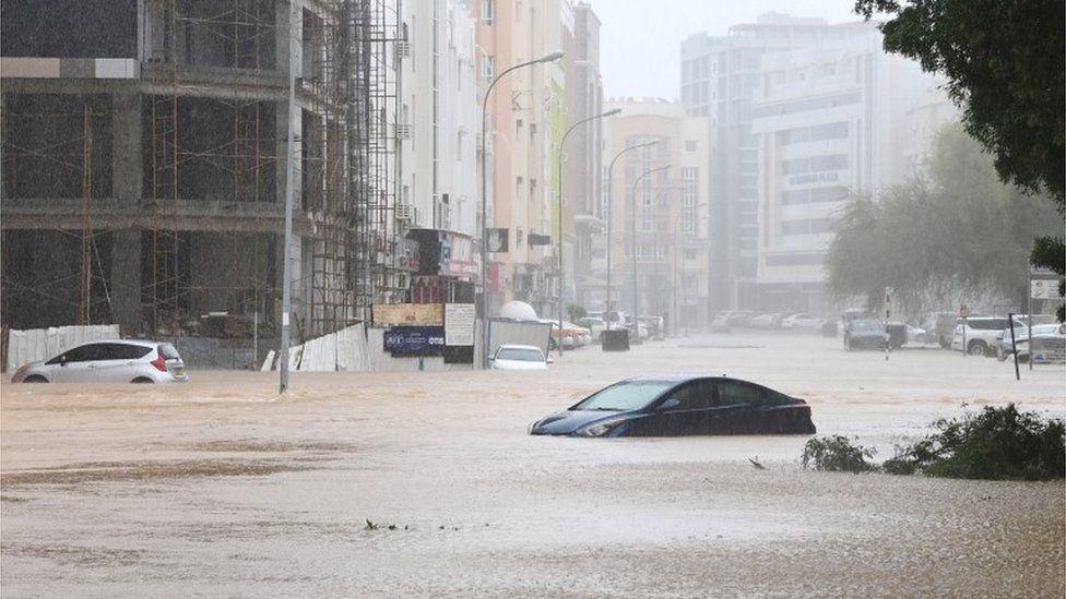 Carros são vistos abandonados em uma rua inundada
