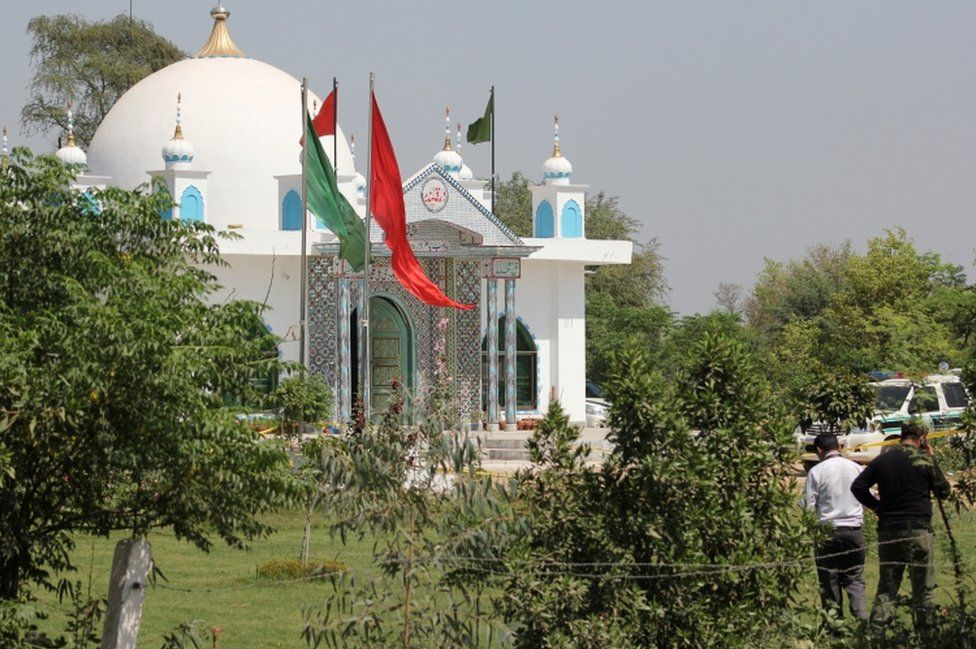 Members of the police forensic unit (R) survey the scene outside the Sufi shrine on the outskirts of Sargodha, Pakistan on 2 April, 2017