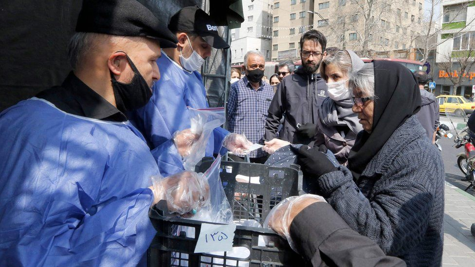 People queue to receive packages of precautions against Covid-19 from the paramilitary Basij force in Tehran, Iran (15 March 2020)
