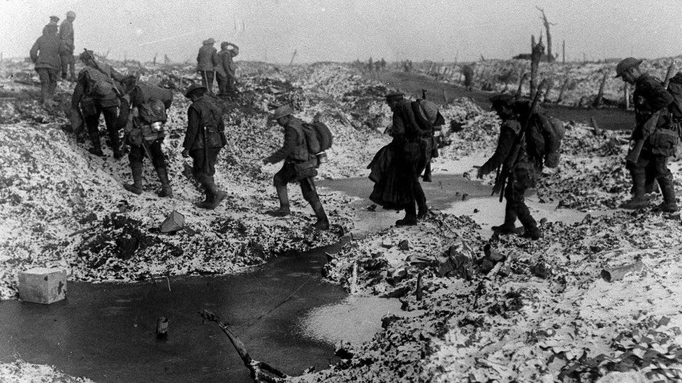 British soldiers negotiating a shell-cratered, Winter landscape along the River Somme