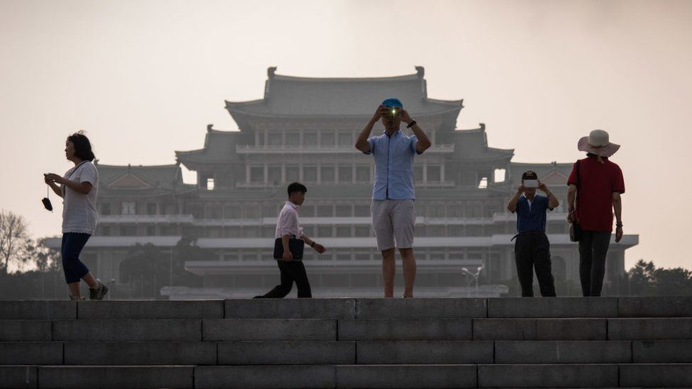 In a photo taken on 19 July 2017 tourists take photos before the Grand People's Study House on Kim Il-Sung square in Pyongyang