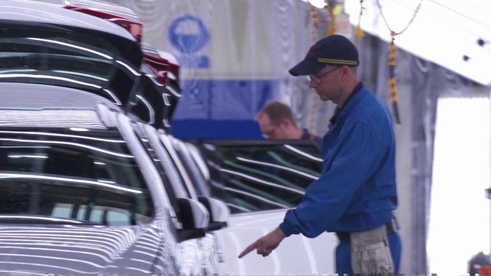 Toyota workers with brand new cars