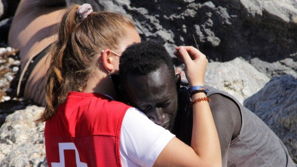 A Spanish Red Cross member hugs a migrant