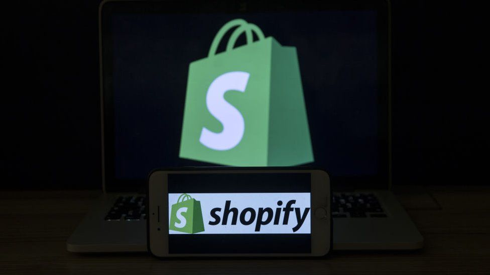 Shopify logo on mobile phone and laptop.