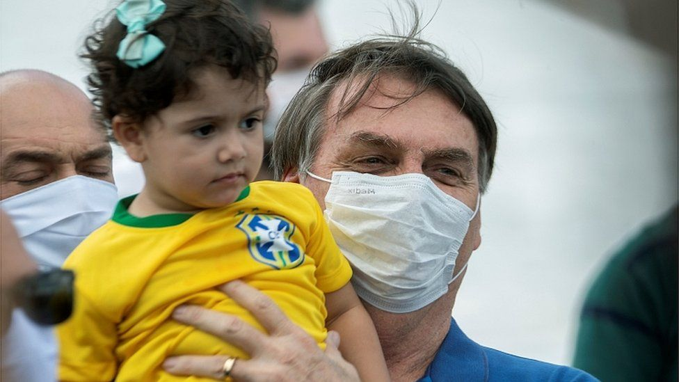 Brazilian President Jair Bolsonaro lifts up a girl during a rally with supporters in Brasilia, 17 May 2020