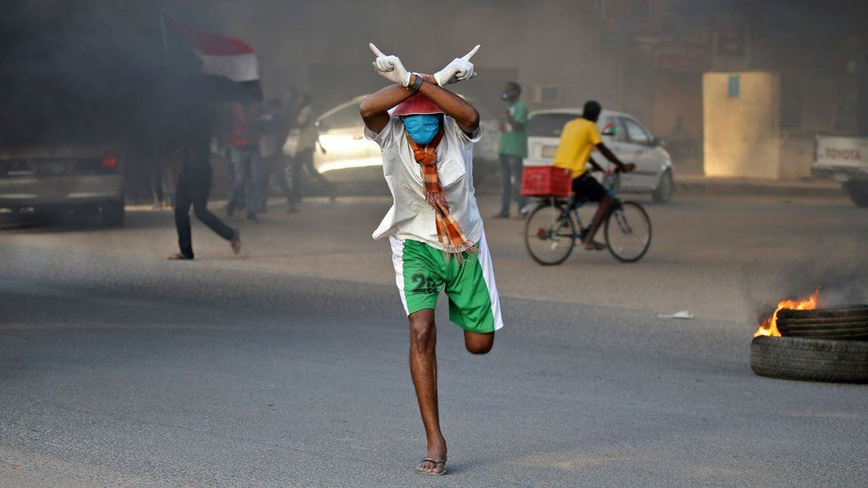 A Sudanese protester clad in mask and latex gloves runs during a demonstration in the Riyadh district in the east of the capital Khartoum on June 3, 2020.