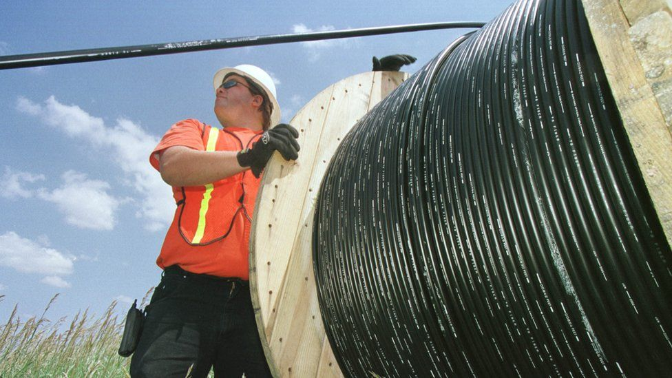 A workman laying fibre optic cable