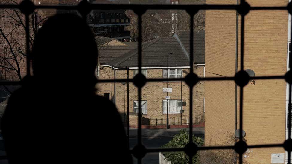Suri, seen in silhouette, looking over Hackney