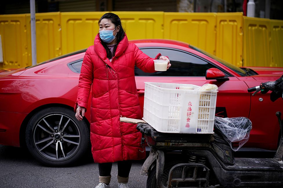 A vendor wearing a face mask sells soup on a street