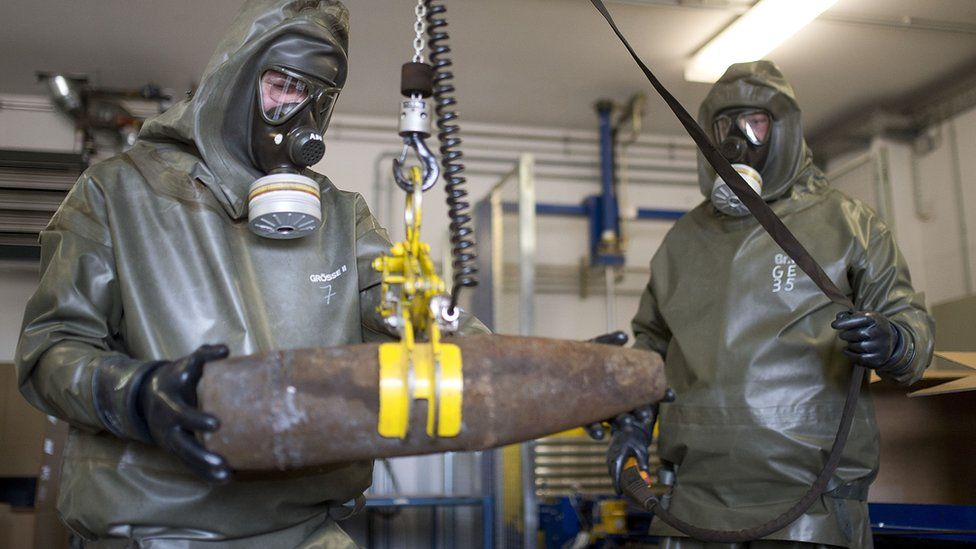 Workers in protective clothing unload a dummy shell during a media day at the GEKA facility in Munster, Germany, on 5 March 2014