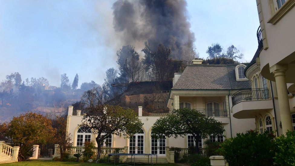 A huge plume of black smoke rises from a burning home on a hilltop beside one still standing in Bel Air, east of the 405 freeway on December 6, 2017 in Los Angeles, California