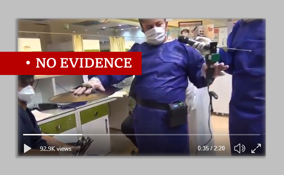 Screenshot of video showing the Iranian device which claims to be able to detect coronavirus. Man in protective clothing holds the device in left hand and cymbal in the other towards the patient.