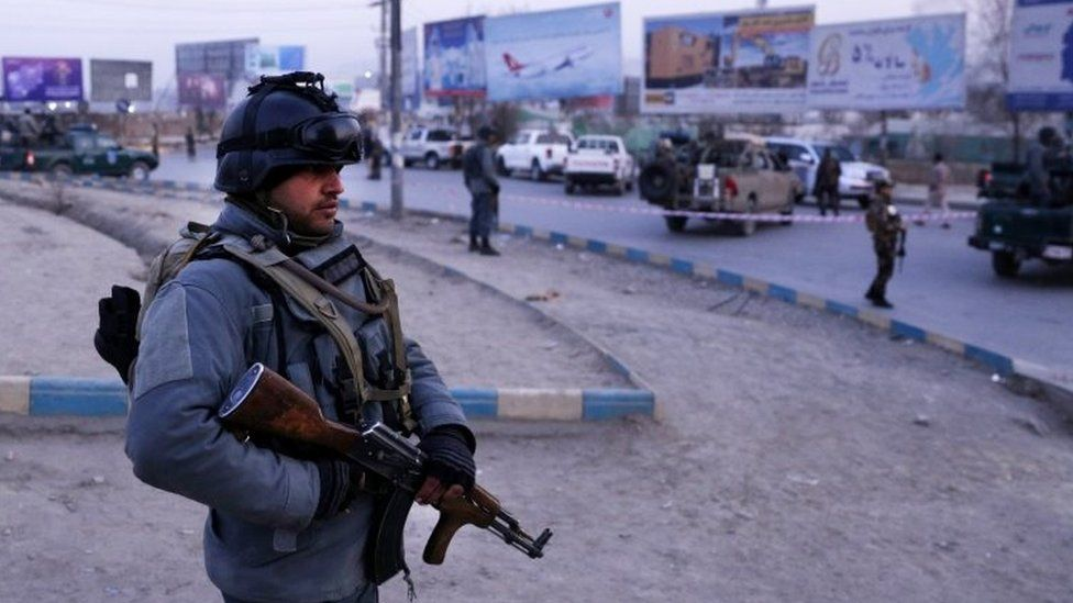 Afghan security officials stand guard at the scene of a suicide car bomb attack in Kabul