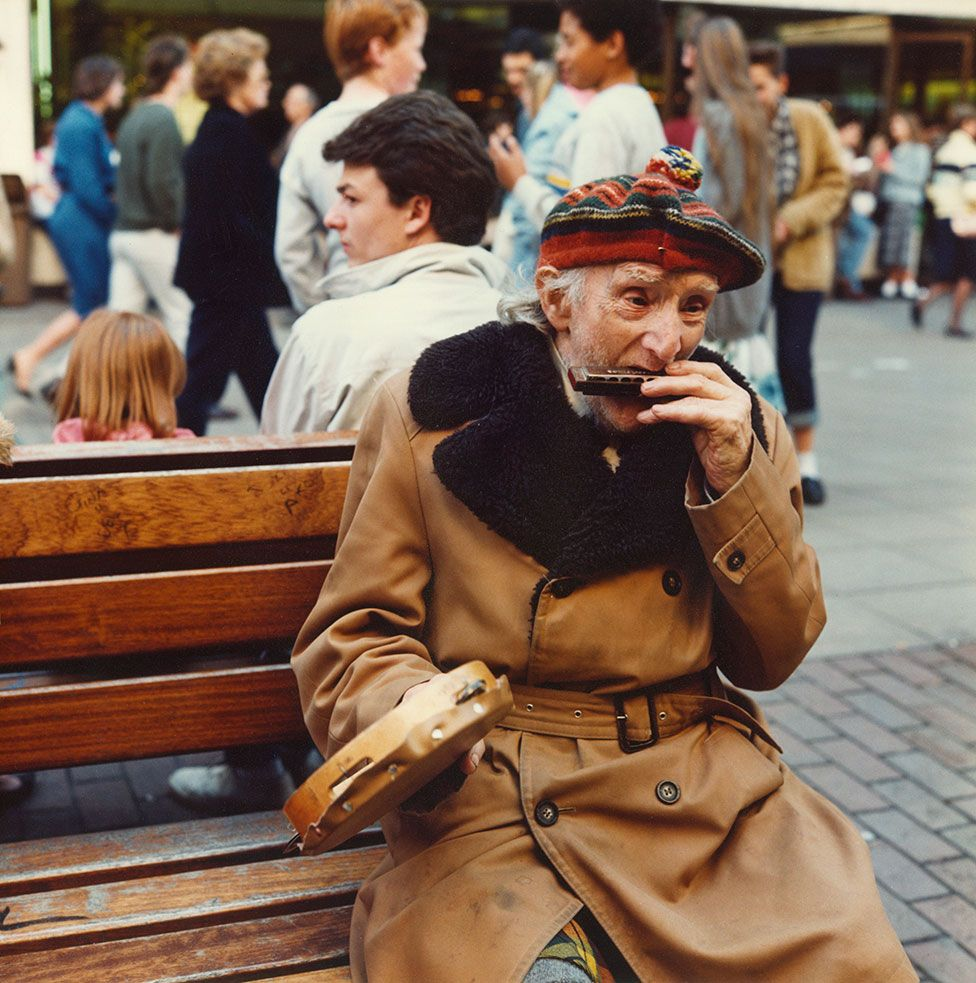 An elderly man sits on a street bench and plays the harmonica