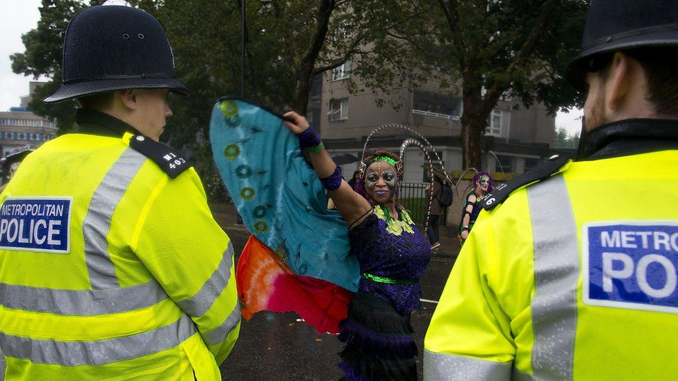 Police officers look on as members of the London Samba School perform during the parade at Notting Hill Carnival