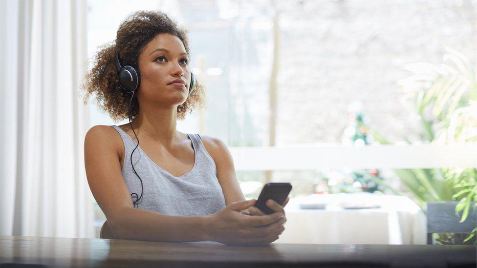 Stok gambar seorang wanita mendengarkan musik