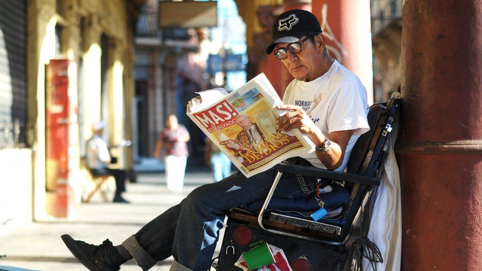 A shoe-shiner reads a newspaper in central San Salvador on 14 March 2013 with news of the election of Pope Francis in its front page.
