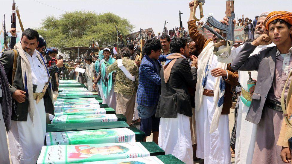 Men raise their rifles next to coffins in the northern Yemeni city of Saada on 13 August 2018