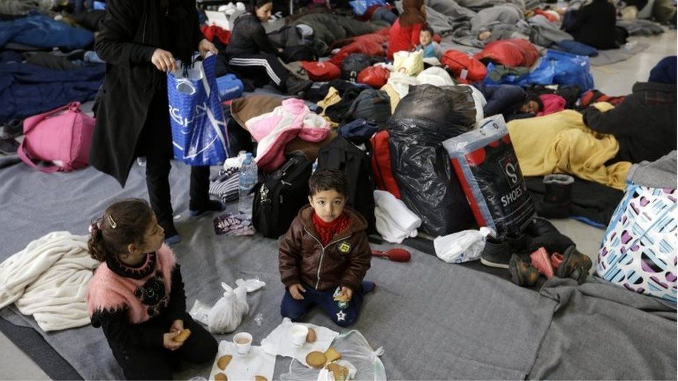Refugees and migrants, who spent another night at a terminal building, wait to be allowed to continue their trip from the Athens port of Piraeus, Friday, Feb. 26, 2016