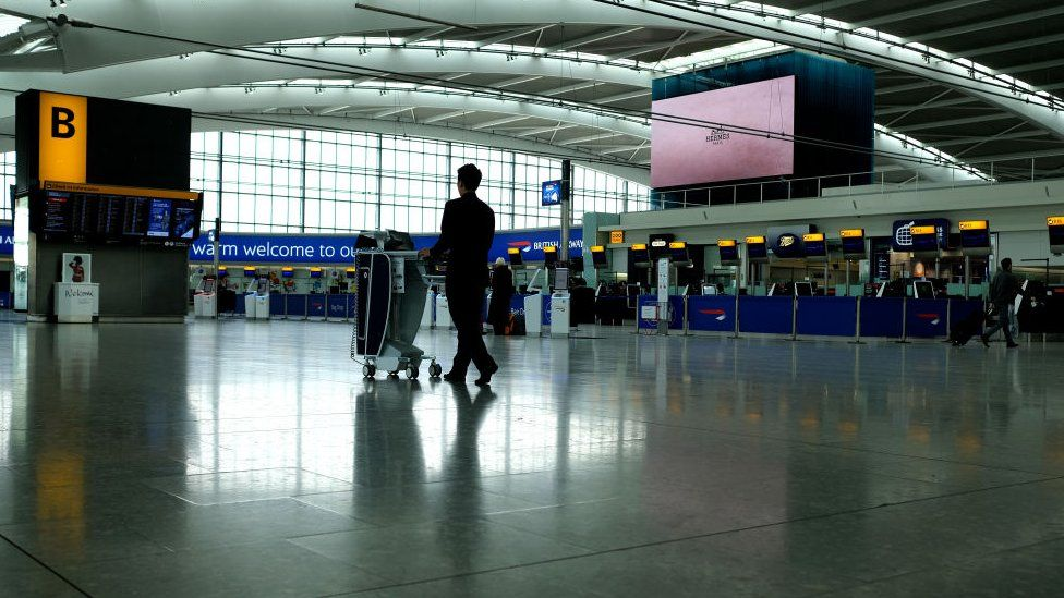 Cleaner pushes trolley through deserted terminal