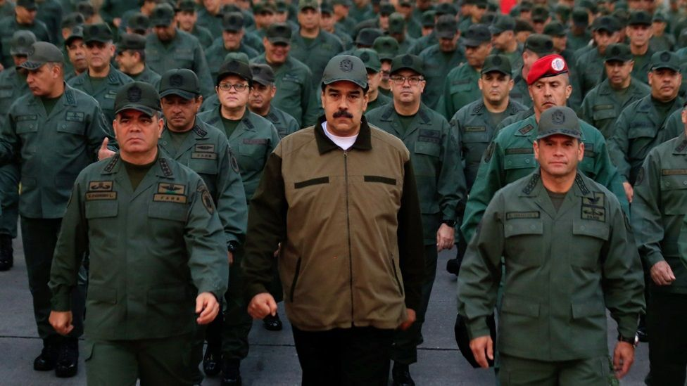 """This handout picture released by Miraflores Palace press office shows Venezuela's President Nicolas Maduro waving military troops accompanied by Defense Minister Vladimir Padrino (L) at the """"Fuerte Tiuna"""" in Caracas, Venezuela on May 2, 2019"""