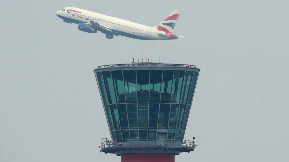 A British Airways plane takes off above the control tower at Heathrow Airport