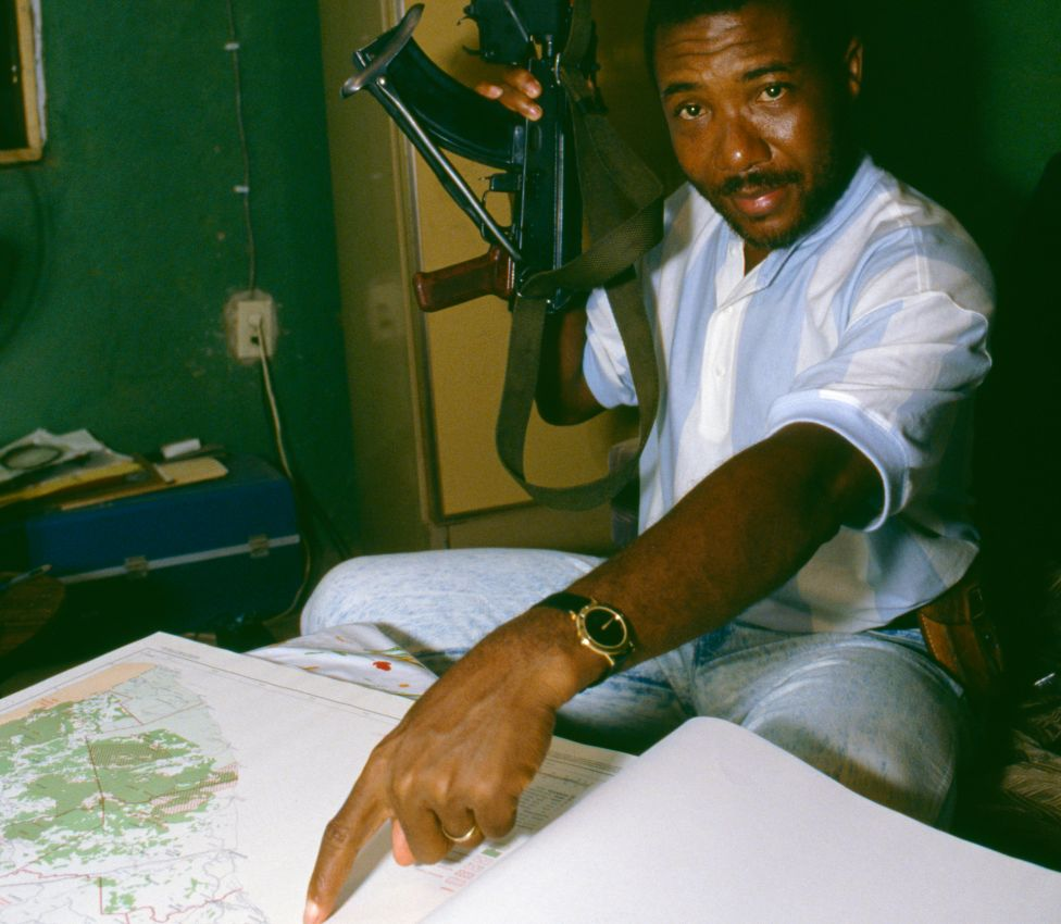 Charles Taylor holding a gun and pointing at a map in 1989, the year he launched a rebellion in Liberia