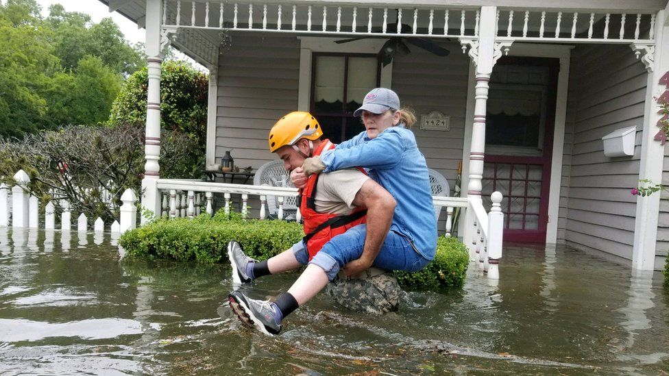 A soldier, waist-deep in water, carried a woman on his back past the front of a house porch