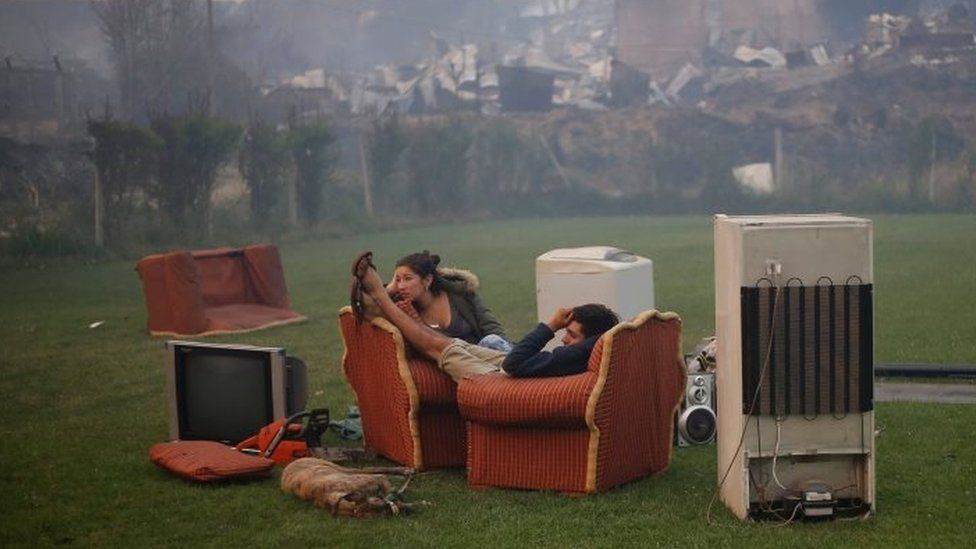 A young couple rest in a football field after a forest fire devastated Santa Olga, 26 January 2017