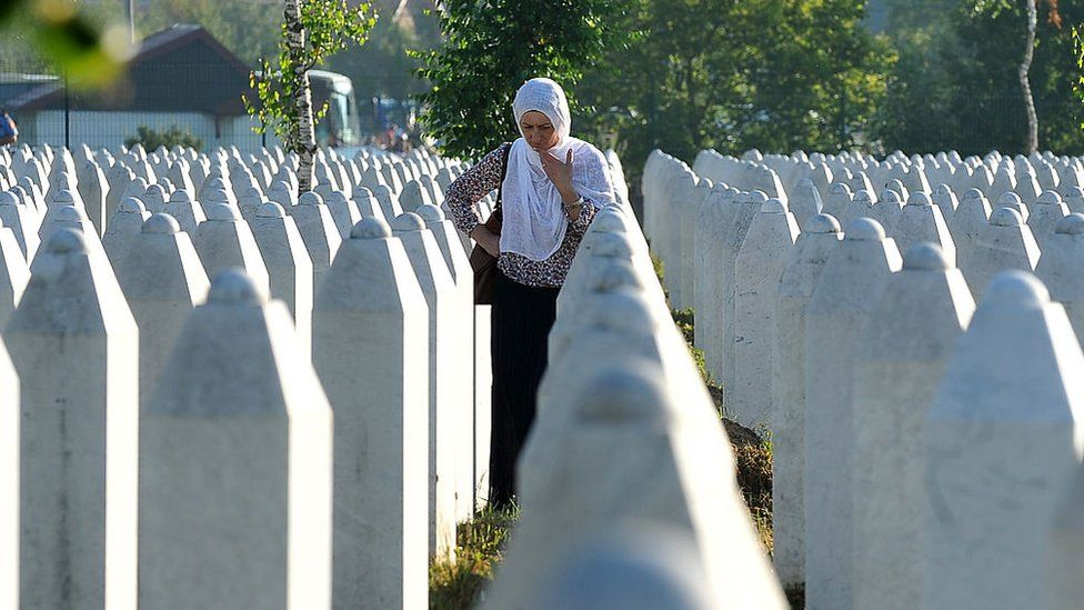 A Bosnian Muslim woman, survivor of Srebrenica 1995 massacre, mourns near graves of her relatives, at the memorial cemetery in the village of Potocari, near Eastern-Bosnian town of Srebrenica