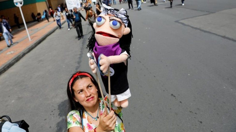 A woman holds a puppet during a protest as a national strike continues in Bogota, Colombia, November 27, 2019