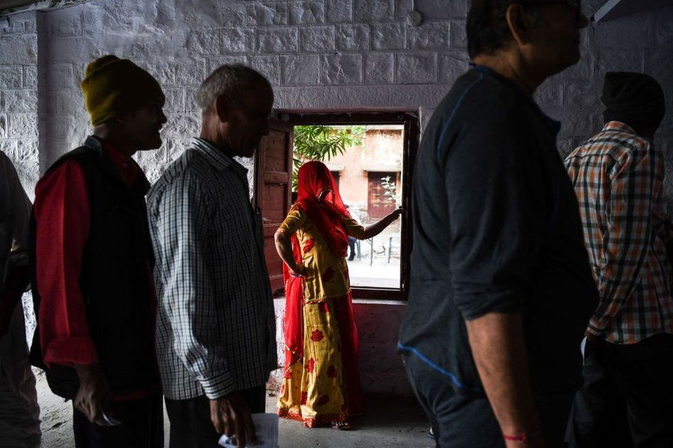 Indians, including a woman, at a polling booth