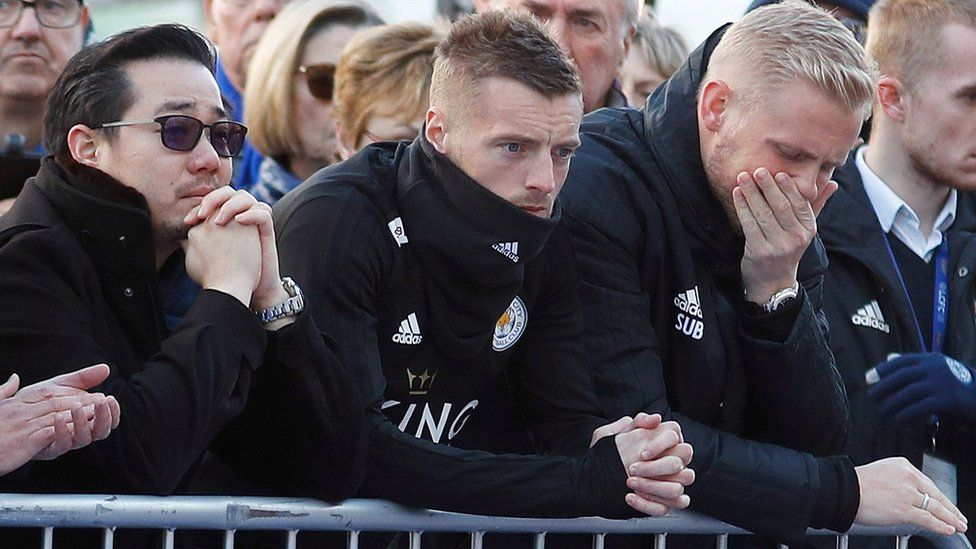 Khun Aiyawatt Srivaddhanaprabha, son of Leicester Citys owner, Jamie Vardy and Kasper Schmeichel look at tributes left for Vichai and four other people