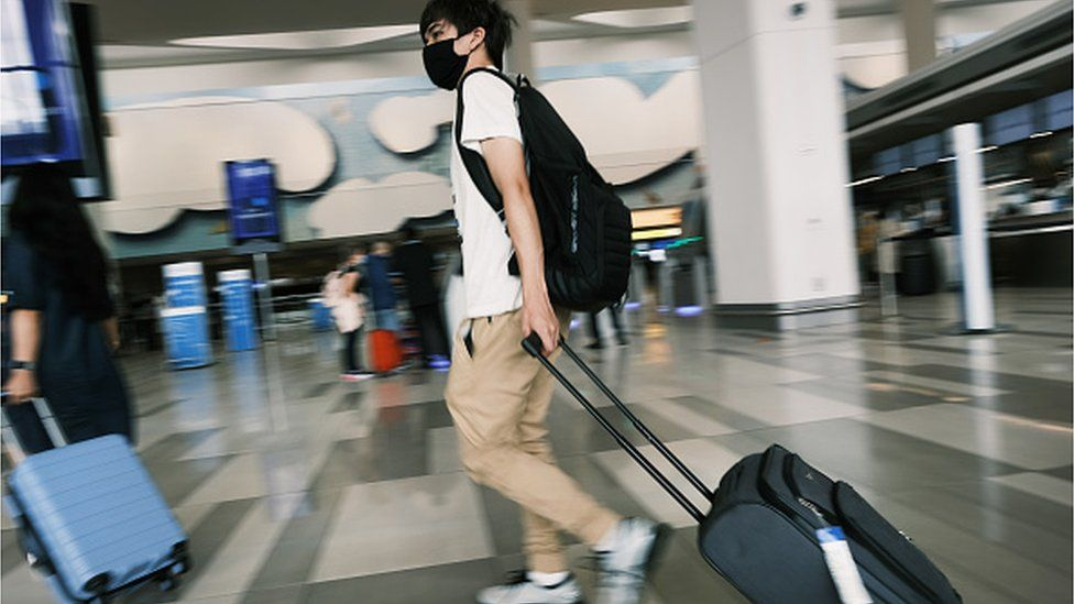 A airport traveller wearing a mask