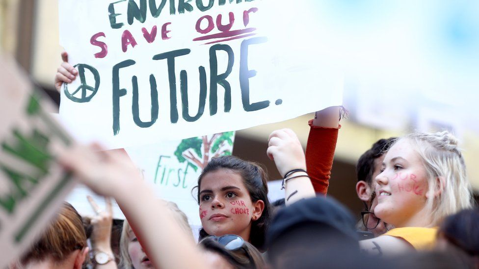 A girl protests in a crowd in Sydney for climate change action