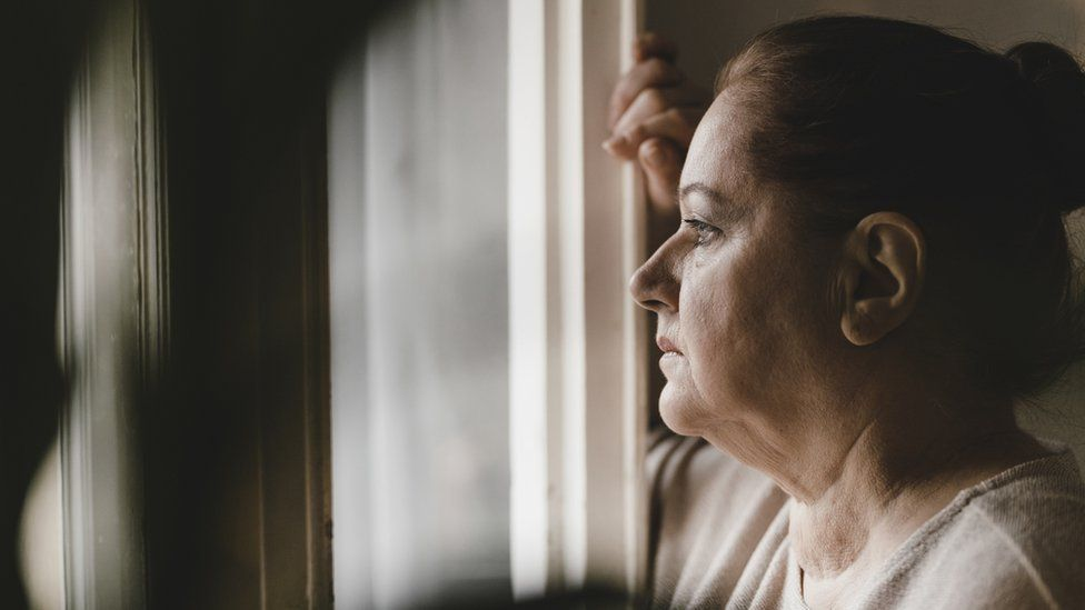 Woman standing at her window