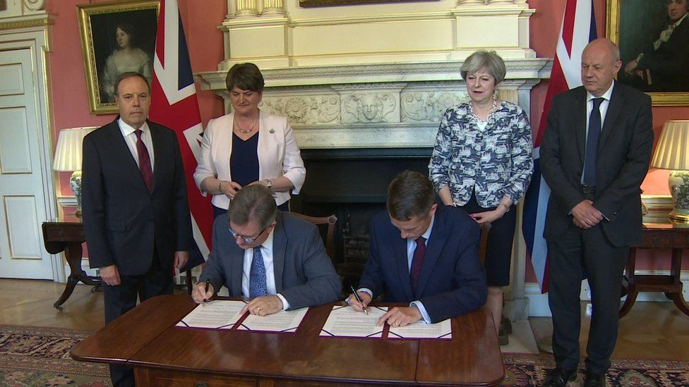 The DUP's Sir Jeffrey Donaldson and Gavin Williamson of the Conservative Party sign a deal in Downing Street