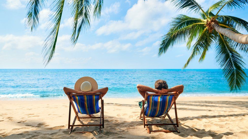 Two people on deck chairs on the beach