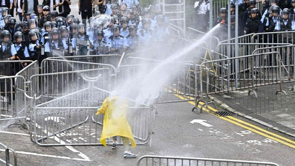 Police officers spray a lone protester near the government headquarters in Hong Kong on June 12, 2019
