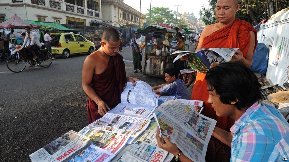 A group of men read newspapers in the Myanmarese capital Yangon in 2014