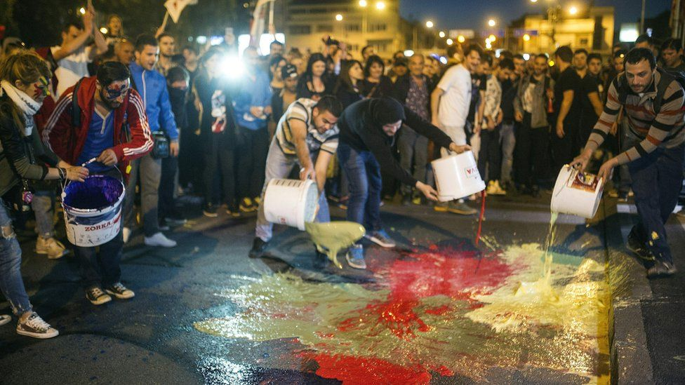 Anti-government protesters pour buckets of paint in front of the government building in Skopje on April 21, 2016 during a massive rally, on the 10th day of protests that have been dubbed the 'Colourful Revolution'.