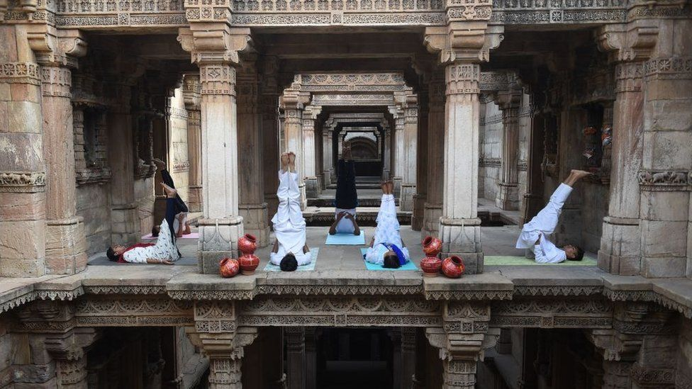 Indian yoga practitioners take part in a yoga session on International Yoga Day at the 15th century Adalaj Stepwell in Adalaj, some 40km from Ahmedabad in western Gujarat state, on June 21, 2019.