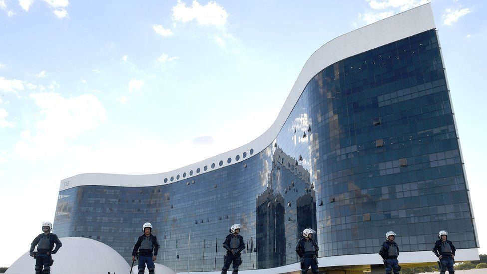 six police officers in riot gear, dwarfed by futuristic glass-fronted court building