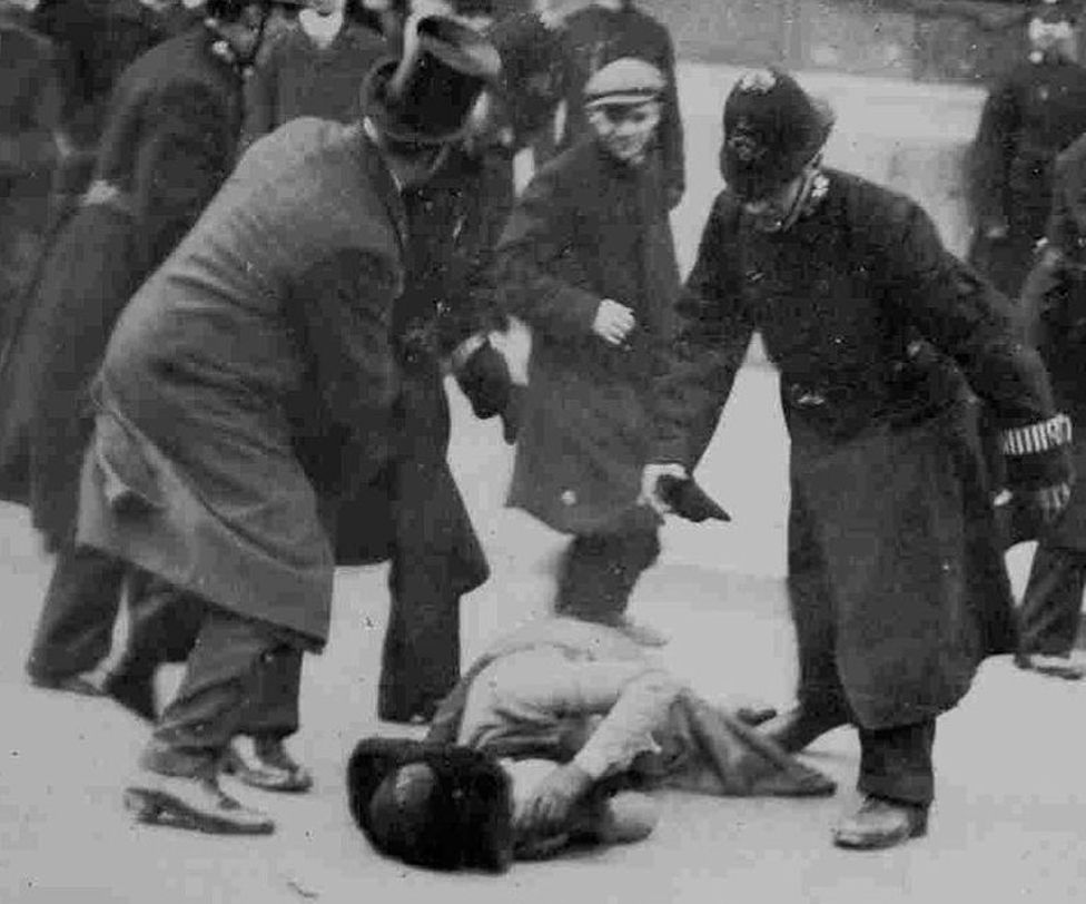 Woman lying on ground after benig injured, surrounded by policemen, 18 November 1910