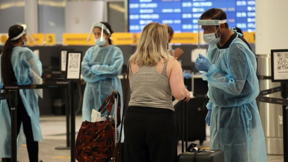 A healthcare worker directs an arriving traveller at Toronto Pearson International Airport