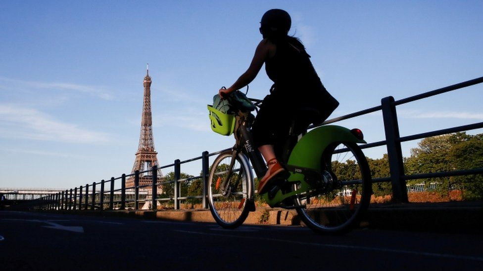 A woman rides a Velib bicycle-sharing service near the Eiffel Tower