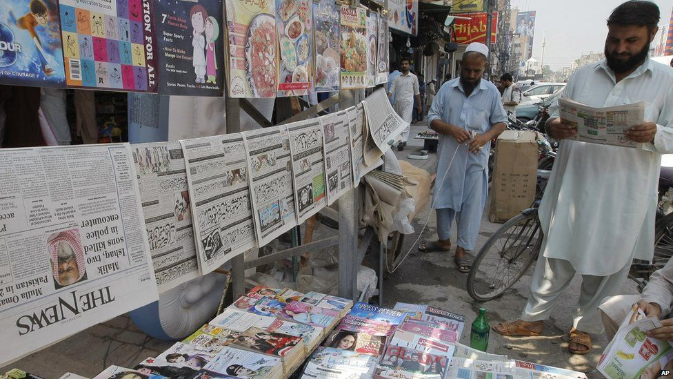 Pakistani men read newspapers at a stand in Peshawar