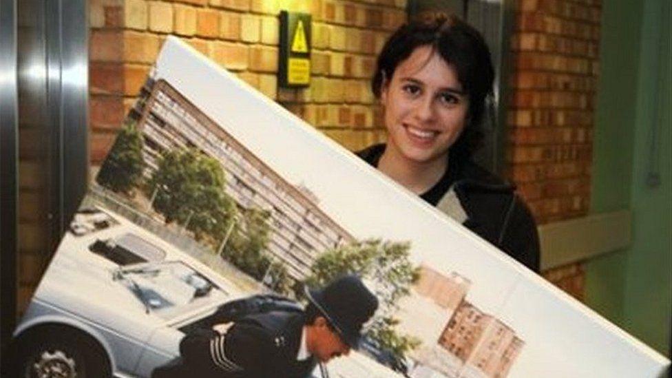 Georgia Macqueen Black holding a photo of a policeman